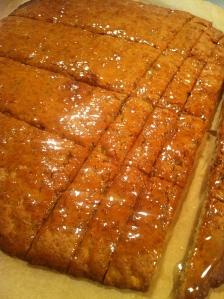 Den bagte lune kage skal pensles med en tynd glasur og skæres ud i stænger mens den er lun. Foto Klinken 2013